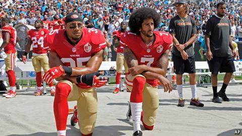 Colin Kaepernick (right) kneeling for the national anthem